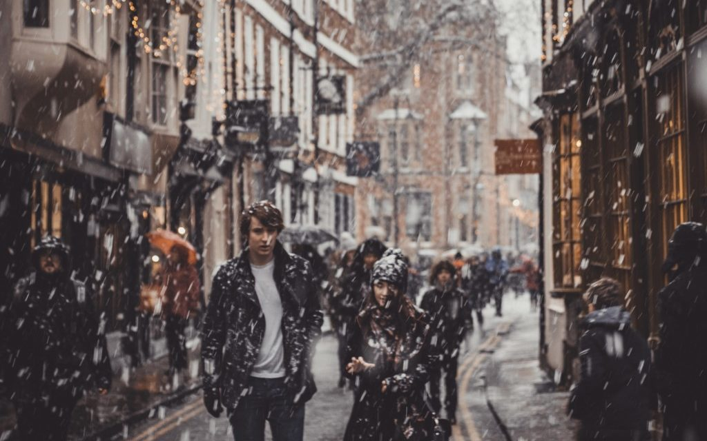 A young couple walks through the snow on the Shambles in York.